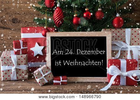Colorful Card For Seasons Greetings. Christmas Tree With Balls And Snowflakes. Gifts In Front Of Wooden Background. Chalkboard With German Text Am 24. Dezember Ist Weihnachten Means Merry Christmas