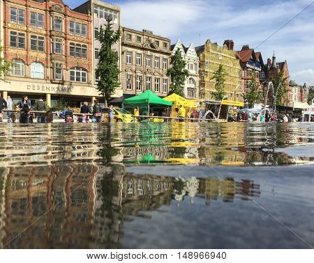 NOTTINGHAM ENGLAND - SEPTEMBER 24: Reflection in water feature of various market stalls in Market Square Nottingham City Centre. In Nottingham England. On 24th September 2016.