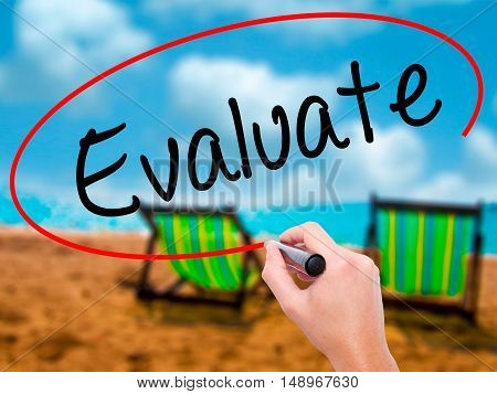 Man Hand Writing Evaluate  With Black Marker On Visual Screen.