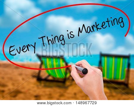 Man Hand Writing  Every Thing Is Marketing With Black Marker On Visual Screen