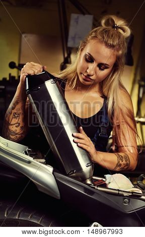 Blond woman mechanic holding a muffler in a motorcycle workshop