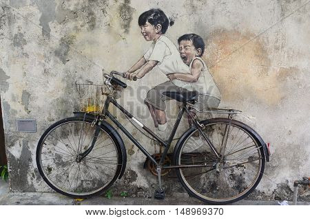 George Town Penang Malaysia - April 18 2016: Little Children on a Bicycle street art mural by Lithuanian artist Ernest Zacharevic in Georgetown Penang in Malaysia.