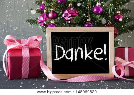 Chalkboard With German Text Danke MeansThank You. Christmas Tree With Rose Quartz Balls, Snowflakes. Gifts Or Presents In The Front Of Cement Background.
