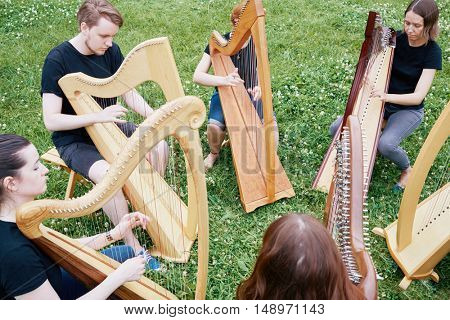 Ensemble of six young musicians play harps outdoors at grassy lawn.