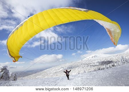 Paraglider starts flying from top of the mountain. Sheregesh resort, Siberia, Russia