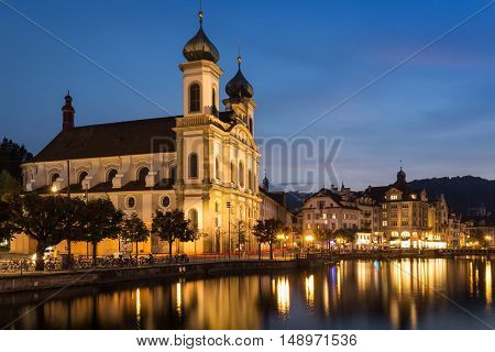 Romantic evening view of the Jesuit Church Lucerne Switzerland with the lights reflected in the tranquil water of the lake under a blue hour twilight sky