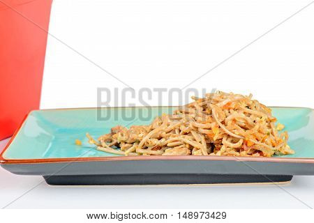 Meat and noodles in blue plate. Red take away box on the background.