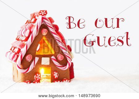 Gingerbread House In Snowy Scenery As Christmas Decoration With White Background. Candlelight For Romantic Atmosphere. English Text Be Our Guest