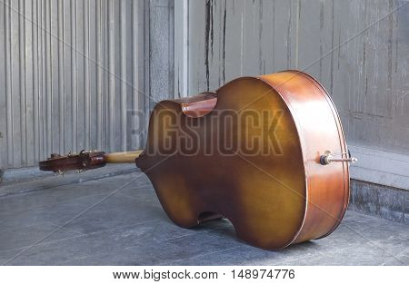 Bass fiddle sitting on its side in an unoccupied corner.