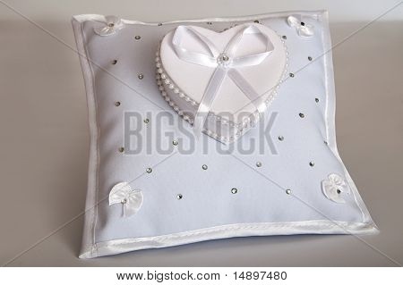 White Pillow For Wedding Rings On The Gray Background