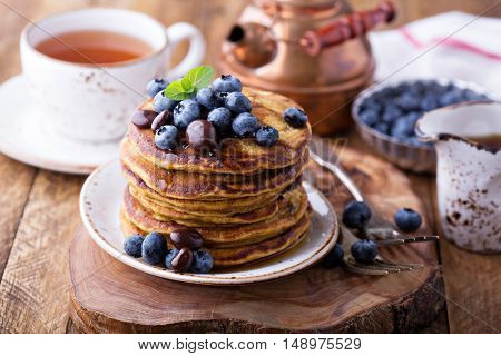 Pumpkin pancakes in high stack with blueberries and syrup served with tea in a rustic setting