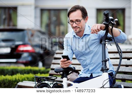 Virtual communication. Handsome bespectacled man putting his hands on bike and using laptop while sitting on the bench.