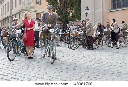STOCKHOLM - SEPT 24 2016: Bicycles and young men and woman dressed in old fashioned tweed and red dress in the Bike in Tweed event September 24 2016 in Stockholm Sweden
