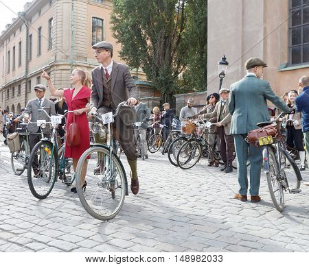 STOCKHOLM - SEPT 24 2016: Young man and woman dressed in old fashioned tweed and red dress with bicycle in the Bike in Tweed event September 24 2016 in Stockholm Sweden