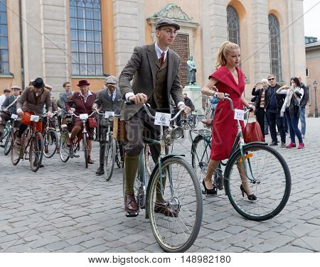 STOCKHOLM - SEPT 24 2016: Young man and woman dressed in old fashioned tweed and red dress cycling in the Bike in Tweed event September 24 2016 in Stockholm Sweden