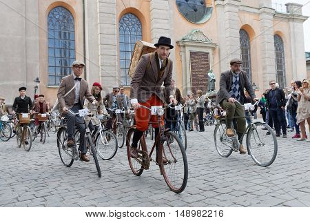 STOCKHOLM - SEPT 24 2016: Group of elegant cycling people wearing old fashioned tweed clothes in the Bike in Tweed event September 24 2016 in Stockholm Sweden