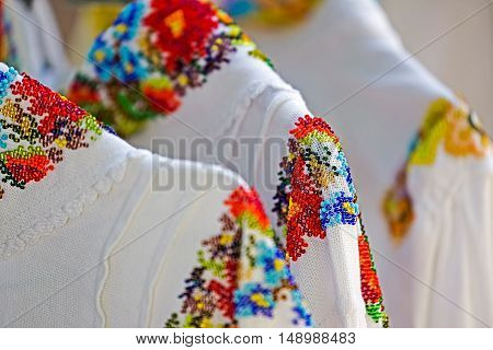 Background with folk motif decoration in beads at women costumes hanging for sale. Specific for Bistrita-Nasaud area Romania.
