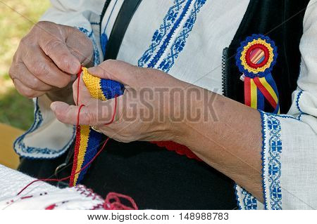 Old woman dressed in romanian traditional clothing interweaves by hand one belt in national colors and design.