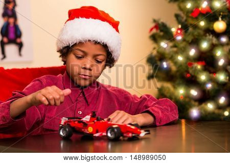 Afro boy with toy car. Kid playing with Christmas present. Checking out the Christmas present. I think he's satisfied.