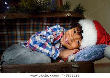 Smiling Christmas kid inside suitcase. Afroamerican kid's happy Christmas smile. Warmness of home. Such days stay in memory.