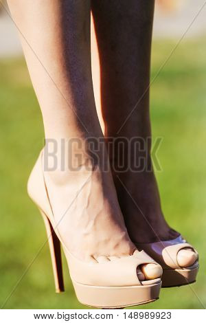 Beige shoes female fashion high heel pumps on woman legs beautiful feet on natural background