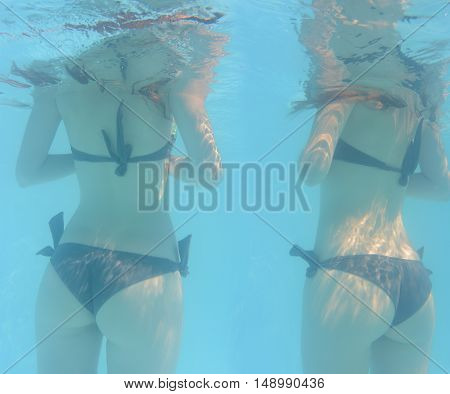Two female bodies of young woman in beautiful identical black sexy bikini standing back underwater in blue transparent clear water of summer pool