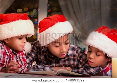 Boys reading book on Christmas. Kids in Santa hats reading. Reading Christmas stories at night. Calm holiday atmosphere.