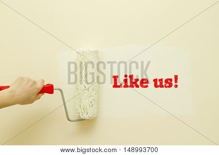 Woman hand painting wall written LIKE US word on it.