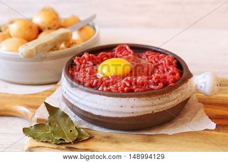 Raw minced meat with egg in ceramic pot and onions