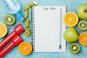 Diet plan menu or program, tape measure, water dumbbells and diet food of fresh fruits on white background. Weight loss and detox concept. Top view, flat lay. poster