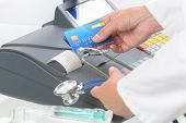 pharmacist or medical doctor holdnig stethoscope and using cash register and credit card at pharmacy or surgery poster