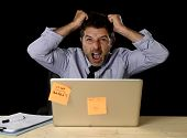 young crazy stressed businessman screaming desperate pulling hair in stress with laptop computer heavy work load isolated on office desk black background in overwork overtime concept poster