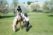 Lady riding on the horse with her trainer outdoors. Natural light and colors poster