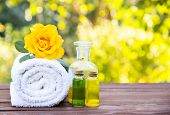 Massage oil, white towel and flower elixirs. Cosmetics for saunas and spa treatments. Spa concept. Essential oils. Cosmetics for saunas and spa treatments. Fragrant yellow rose. Copy space. poster