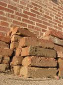 A pile of red bricks in front a brick exterior wall. poster