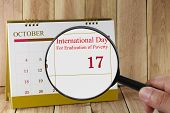 Magnifying glass in hand on calendar you can look International Day For Eradication of Poverty on 17 October concept of a public relations campaign economy and society. poster