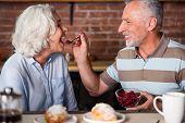 Oldies-Goldies. Elegant old couple having fun during breakfast eating raspberry poster