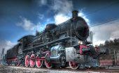Old Steam Locomotive below cloudy blue sky poster