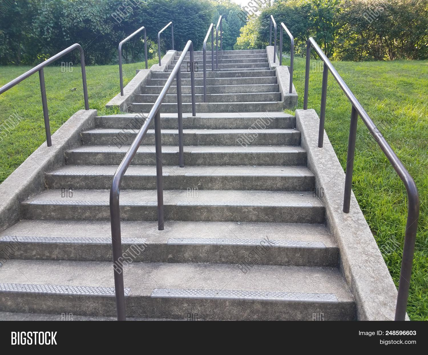 Cement Steps Or Stairs With Metal Railing And Green Grass