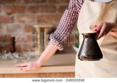 morning coffee tradition. caffeine addiction. strong hot beverage freshly brewed in a jezve or turkish pot in woman hands poster