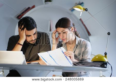 Young Couple Reviewing Invoices And Doing Family Business Plan. Concept Of Money And Economic Proble
