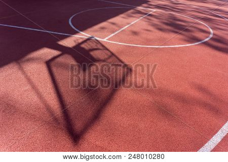 Shadow On The Court Of Basketball Basket With Chains On Streetball Court.
