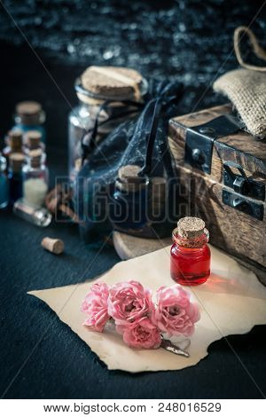 Love Potion. Magic Concept Wit Red Liquid In Small Bottle, Wooden Box, Old Paper And Flowers