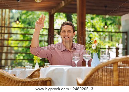 Waiting For Wife. Good-looking Man Wearing Nice Pink Shirt Sitting In Restaurant Waiting For Wife