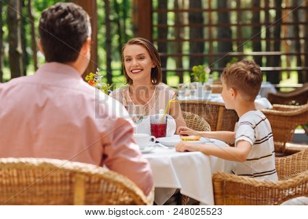 Family Woman. Beaming Family Woman Looking At Her Husband And Son While Discussing Plans For The Upc