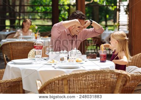 Joking with girl. Dark-haired loving father feeling unbelievably amazing while joking with his little girl poster