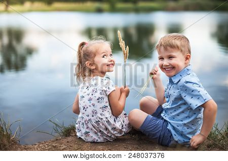 Your Happy Kids, Girl And Boy Are Sitting Near Lake