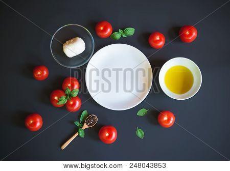 Caprese Salad Ingredients Around Empty Plate On Dark Background