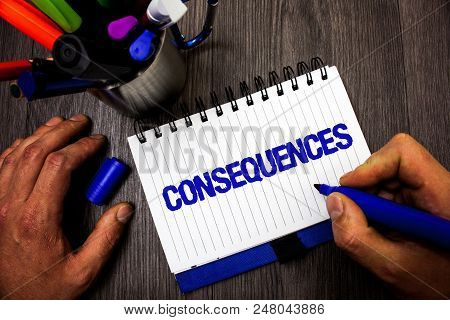 Handwriting text writing Consequences. Concept meaning Result Outcome Output Upshot Difficulty Ramification Conclusion Man hold holding marker notebook ideas markers wooden table inspiration poster