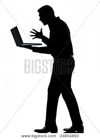 one caucasian business man computing computer laptop angry displeased silhouette standing Full length in studio isolated on white background